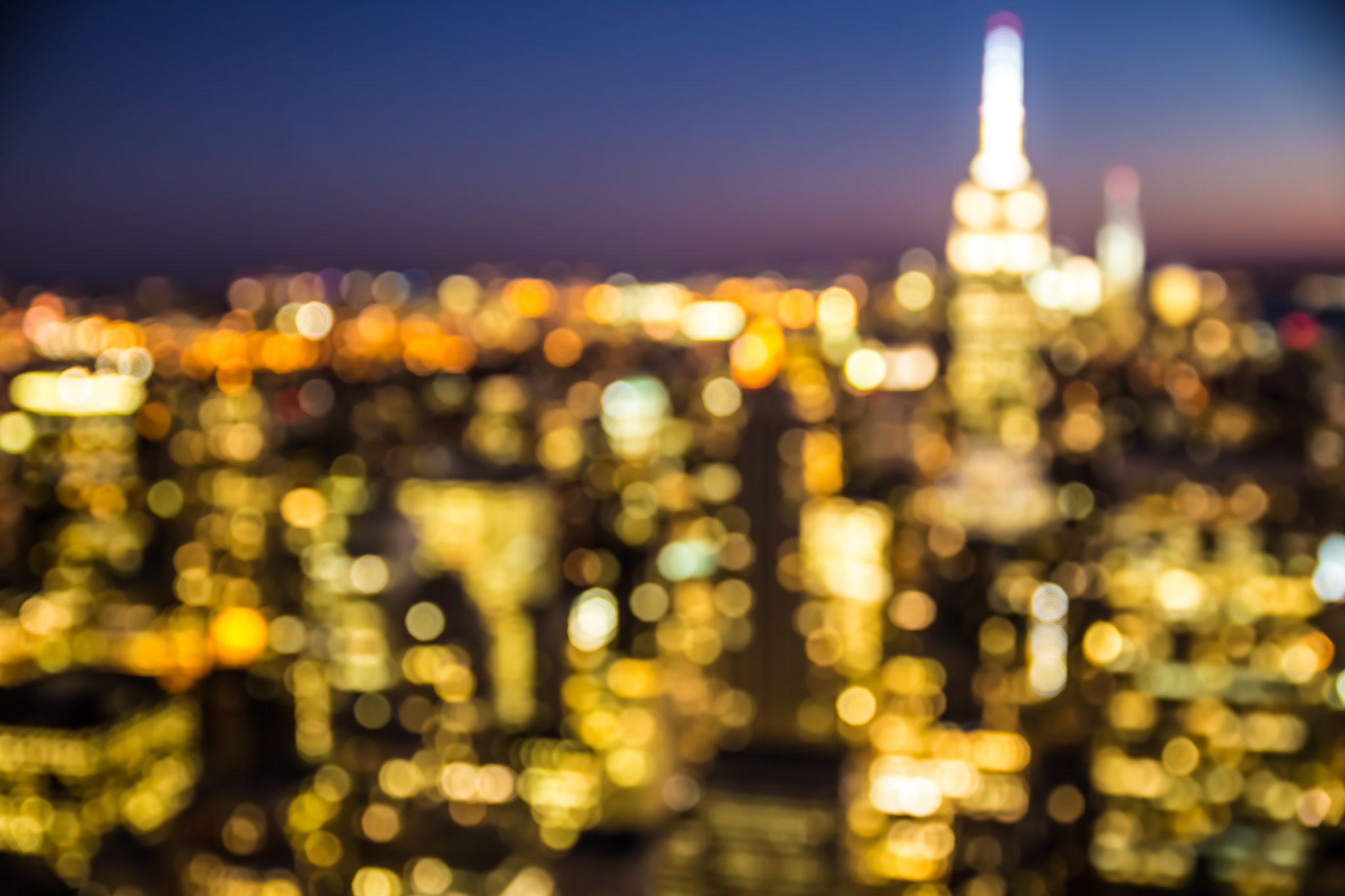 Home / About Artexpo / Defocused Blur Of New York City Buildings Lights At  Night